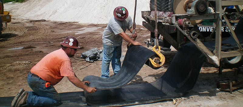 Two workers gently lay down conveyor belt at job site