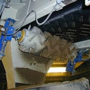Conveyor belt brush installed below conveyor system
