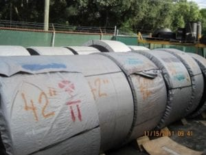 Rolls of conveyor belts outdoors in yard