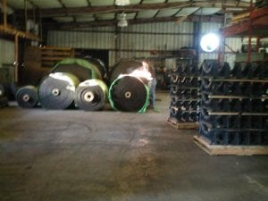 Giant warehouse with conveyor belt system parts and rolls of conveyor belts