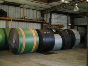 Rolls of different colored conveyor belts on the ground