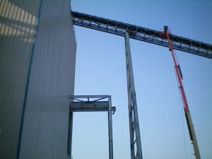 Crews installing conveyor cover on large belt system with crane