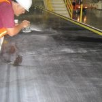 Worker sanding Gypsum wallboard belt