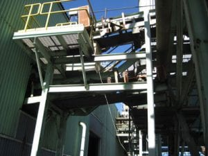 Exterior view of newly installed stainless steel conveyor system with galvanized trough frames