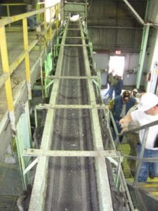 Top view of old conveyor system in power plant as worker inspects the side