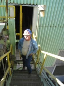 Worker stands outside of old conveyor system exterior facility