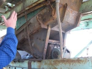 Closeup of worker inspecting old rusted conveyor system components