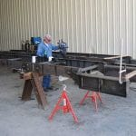 Worker in fabrication warehouse building steel chassis for conveyor system
