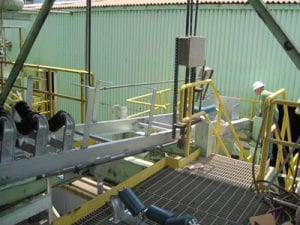 View of vibratory hoppers installed on galvanized trough frames, workers installing conveyor system