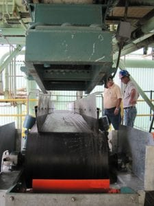 Two workers inspect a conveyor system