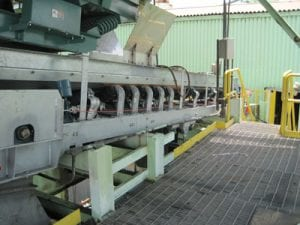 Side view of new stainless steel conveyor system with galvanized trough frames