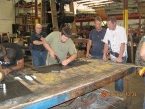 Workers gather around table to splice conveyor belt