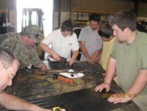 Workers gather around table to fix conveyor belt splices