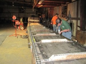 Fabrication workers install refurbished conveyor chain