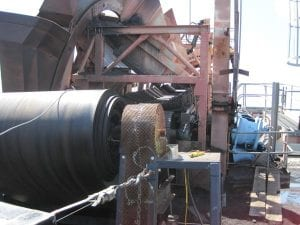 Workers using a winder to remove an old belt from a conveyor system